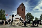 White wedding carriage in front of a church in Denmark.