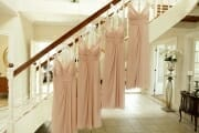 Bridesmaid dresses hanging on the staircase.