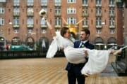 Groom carrying his bride at the streets of Copenhagen.